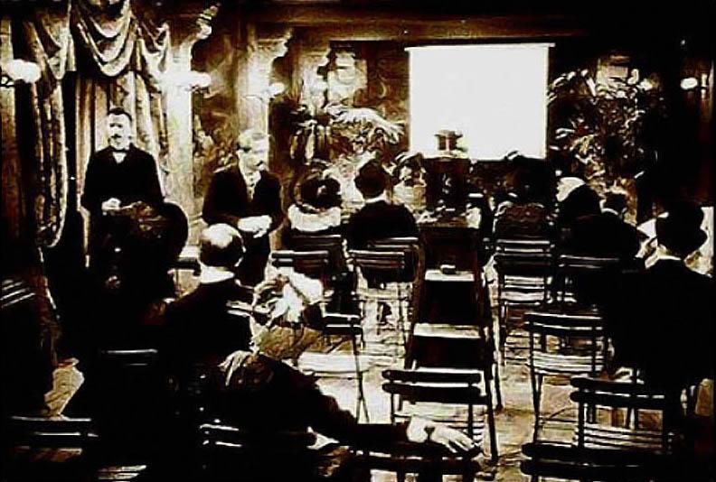 บรรยากาศการฉายหนังขึ้นจอครั้งแรกที่ห้อง Salon Indien โดยมีสองพี่น้องตระกูลลูมิแอร์ยืนอยู่ทางซ้ายของภาพ (Photo credit: www.pariscinemaregion.fr)